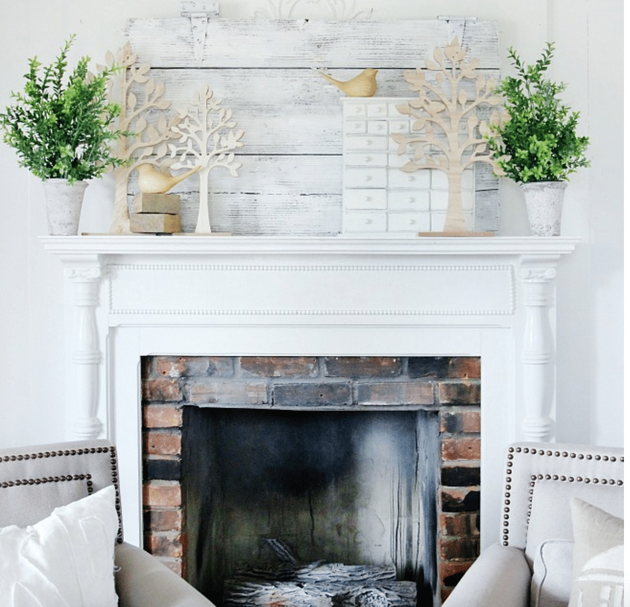 spring mantel decor with tree cut outs, greenery, and bird figurines