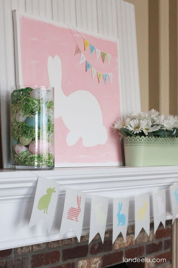 Easter fireplace mantel decor with a bunny picture, a canister of eggs and grass, and garland