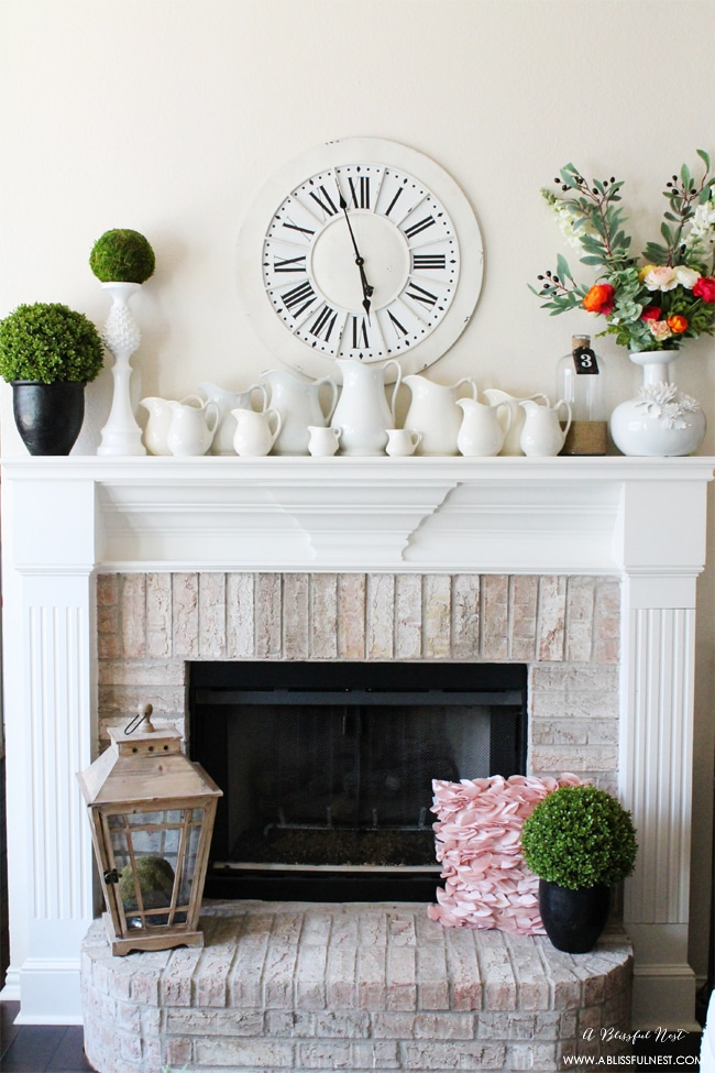 spring mantel decor that includes greenery, blooms and pitchers of various sizes