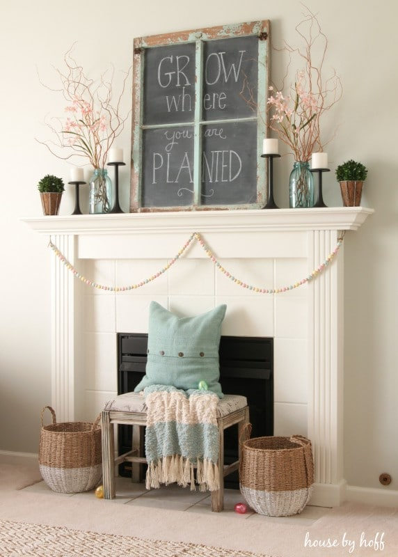 chalkboard sign on a mantel with blue mason jars holding pink springtime blooms