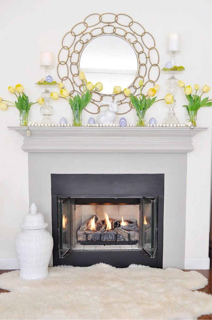 lovely springtime mantel decorations with yellow tulips and a circle mirror