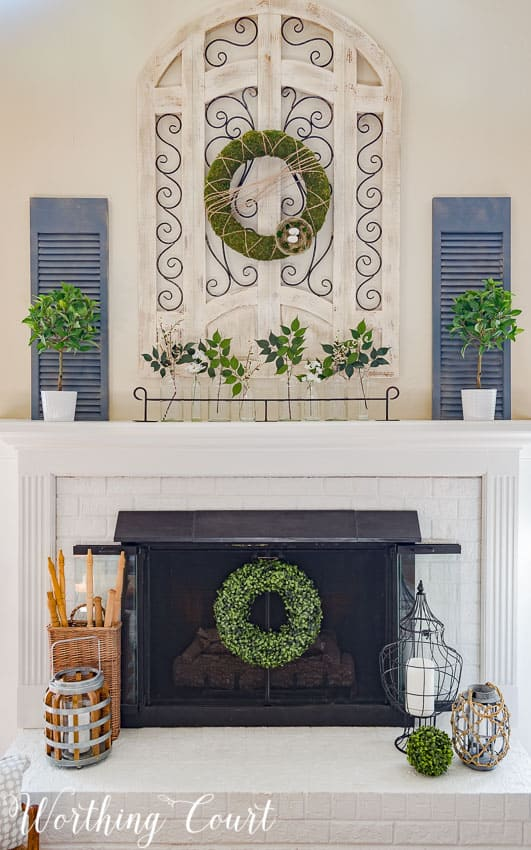 modern farmhouse spring mantel design with boxwood wreaths and other greenery