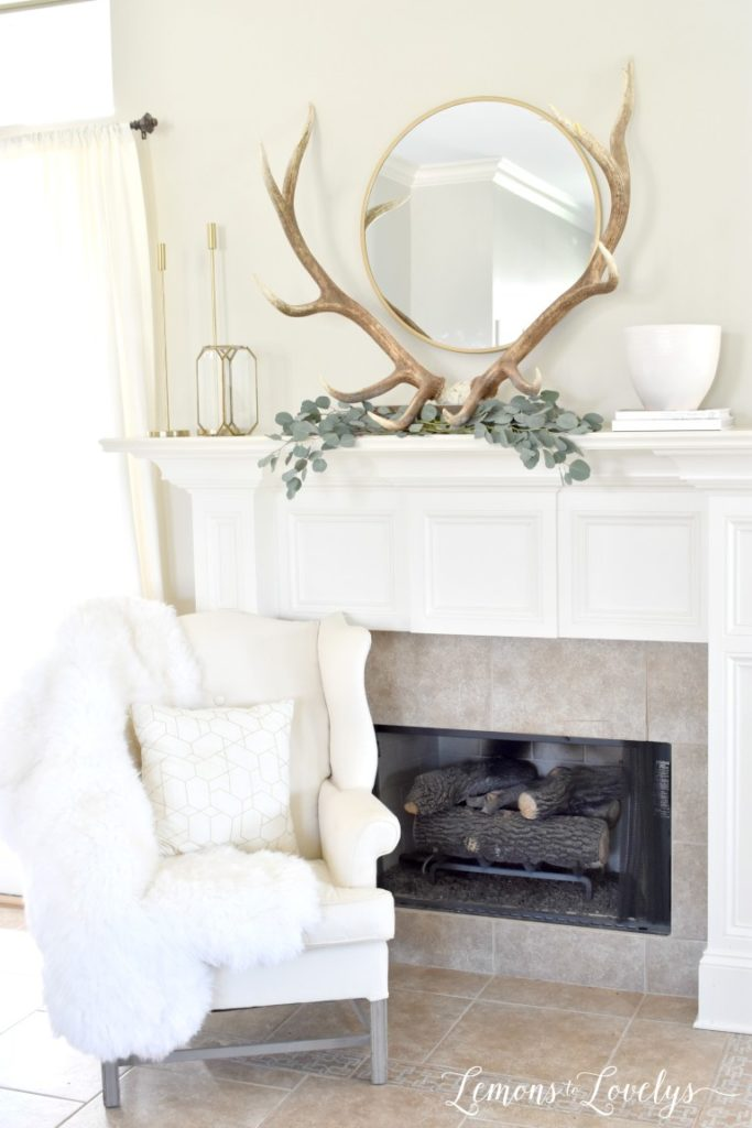 spring mantel decor with antlers, eucalyptus leaves, and a circle mirror