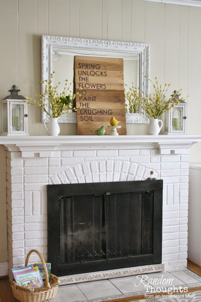 forsythia blooms on a white fireplace mantel with a sign and bird figurines