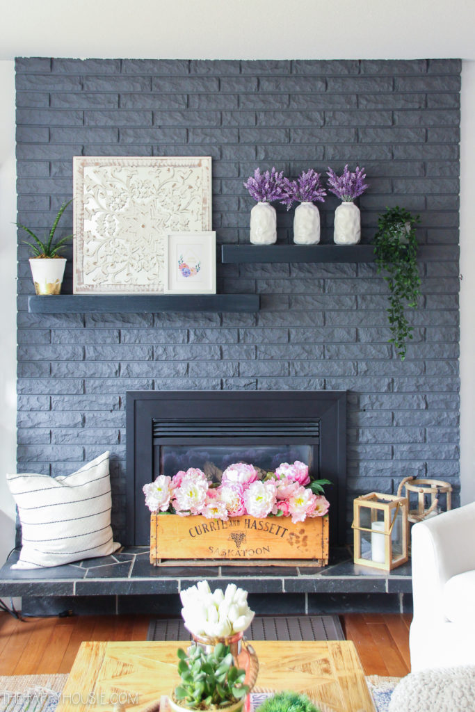dark gray brick fireplace with spring flower blooms on mantel