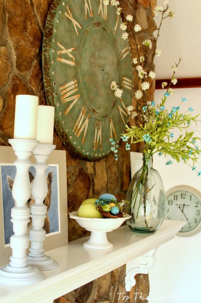 spring mantel design with candles, bright yellow and blue blooms and colored eggs