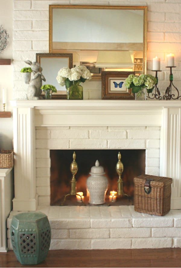 a mix of old and new in spring mantel decor with antique pieces and flower blooms