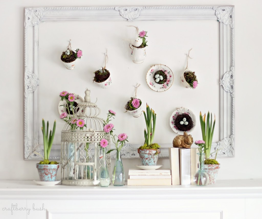 teacups hanging on the wall over fireplace mantel holding spring blooms