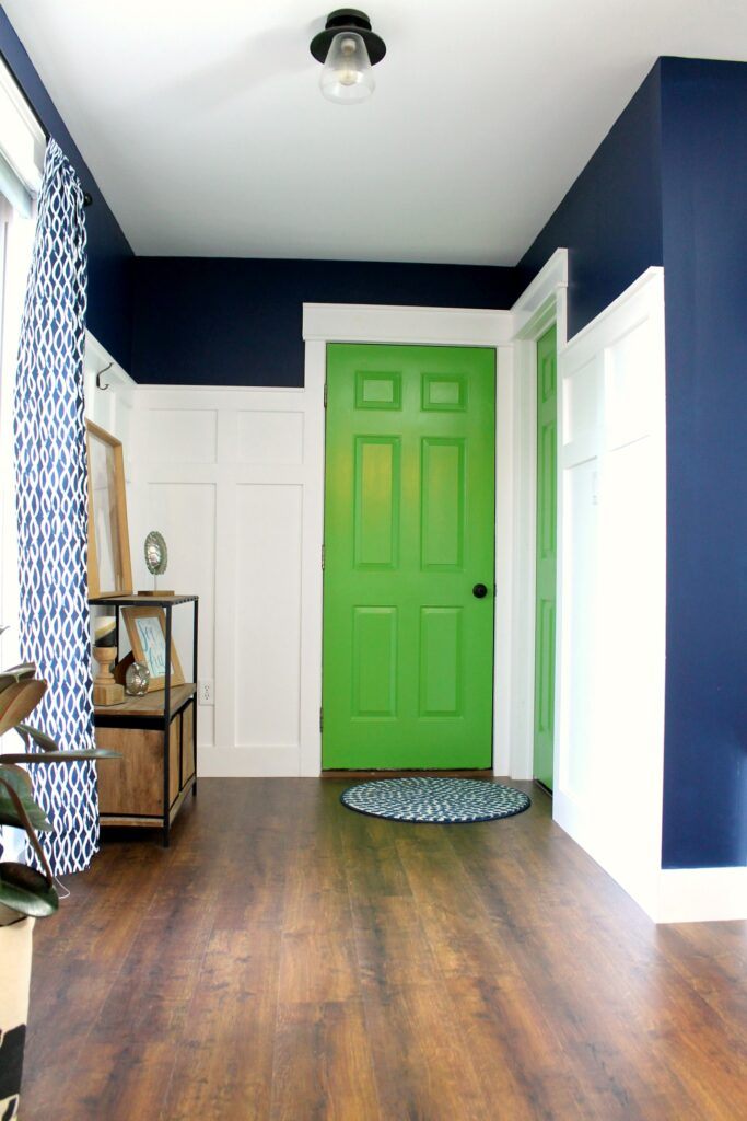 mud room with navy walls, white trim, and bright green interior doors