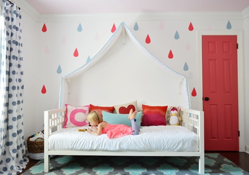 child's bedroom with a poppy red closet door and a girl on the bed