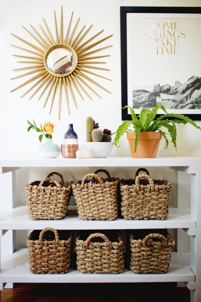Styled entryway with shelving unit, baskets and plants.