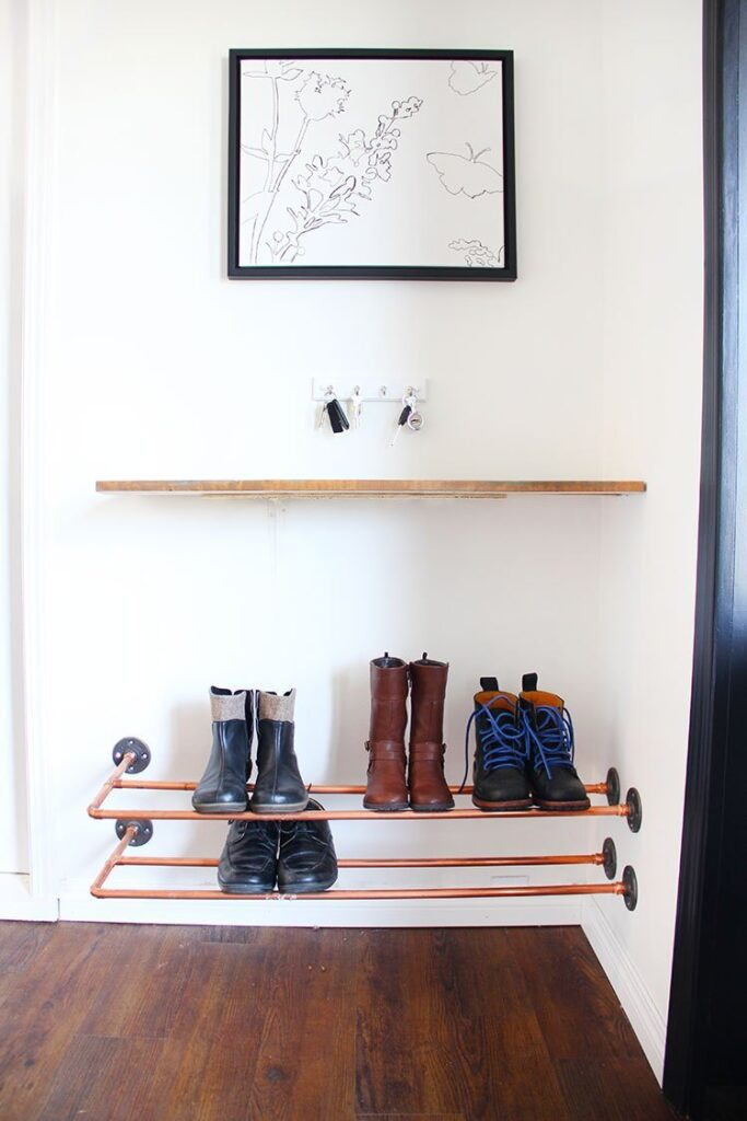 Small entryway shoe storage ideas: DIY wall-mounted copper pipe rack for shoes, a shelf and hooks for keys.