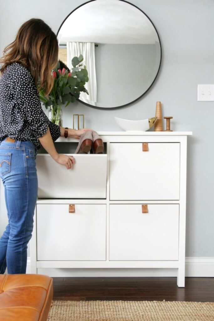 IKEA shoe cabinet dressed up with leather pulls and a large round mirror.