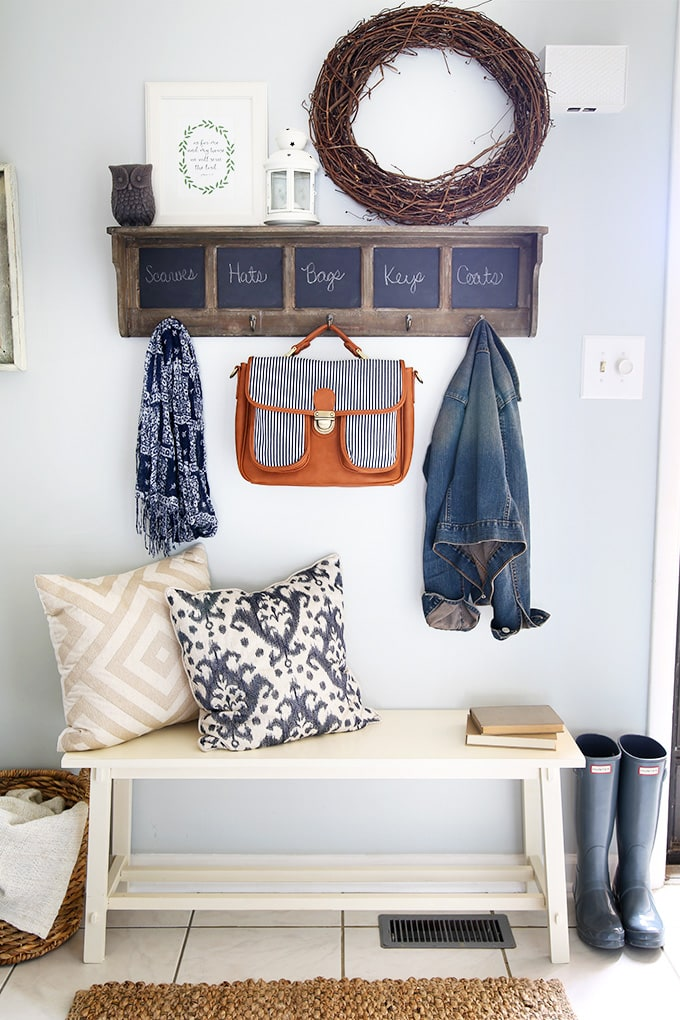 Styled shelf with hooks and chalkboard labels. Bench with throw pillows makes this entryway look cozy.