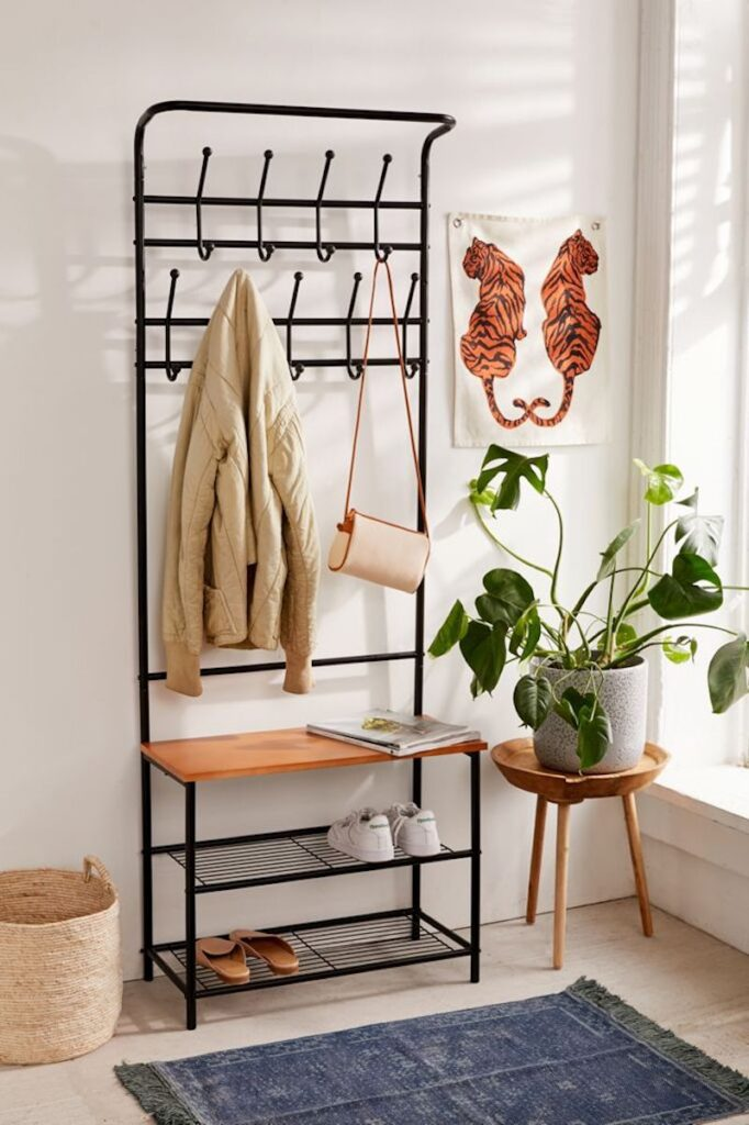All-in-one entryway storage rack, styled with a plant and tiger art piece.