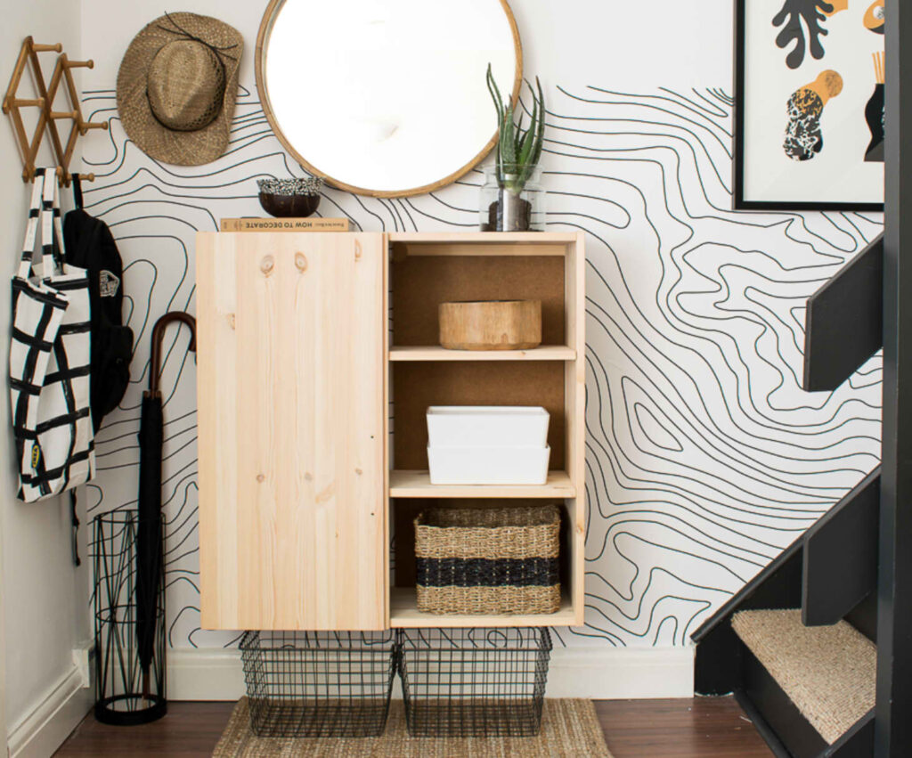 Wall-mounted IKEA cabinet, accordion wall hooks, baskets and umbrella holder keeps all belongings corralled in a small space.