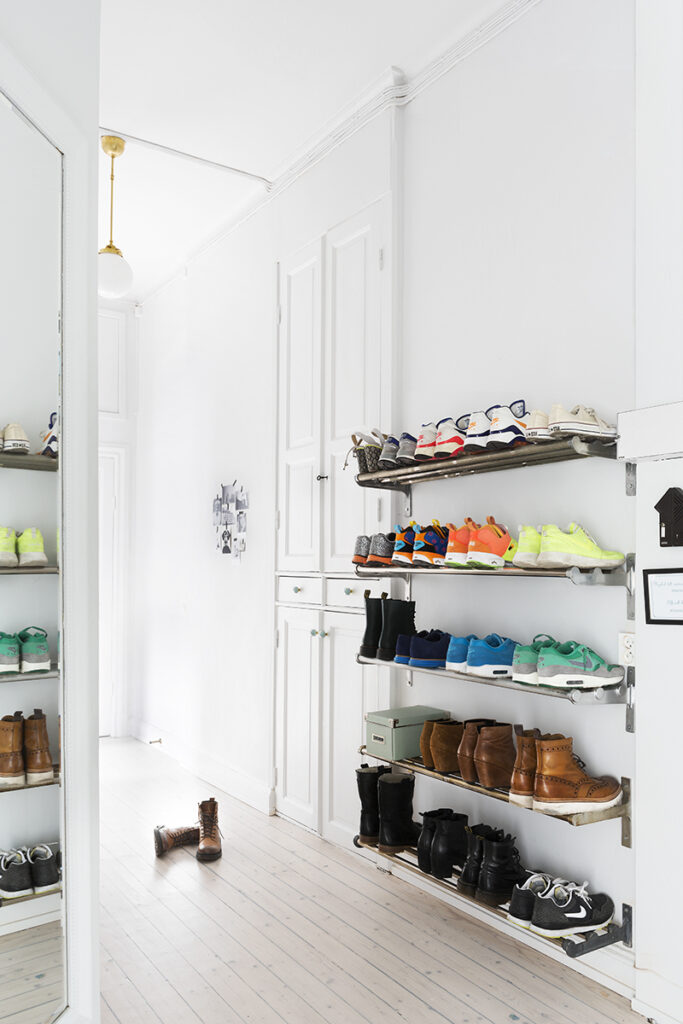 Entryway shoe storage ideas: industrial-style, wall-mounted shoe racks keep shoes organized and off the floor.