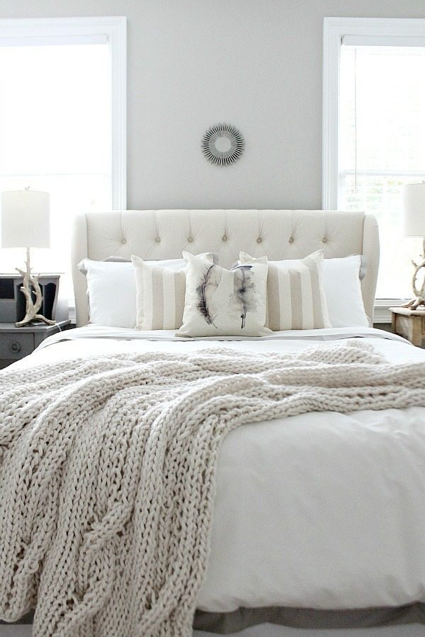 Peaceful bedroom with an off-white decor palette and Sherwin Williams Mindful Gray wall color.