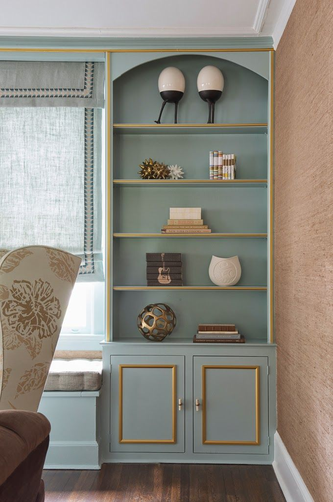 Benjamin Moore Rhine River painted on a built-in bookcase with gold trim.
