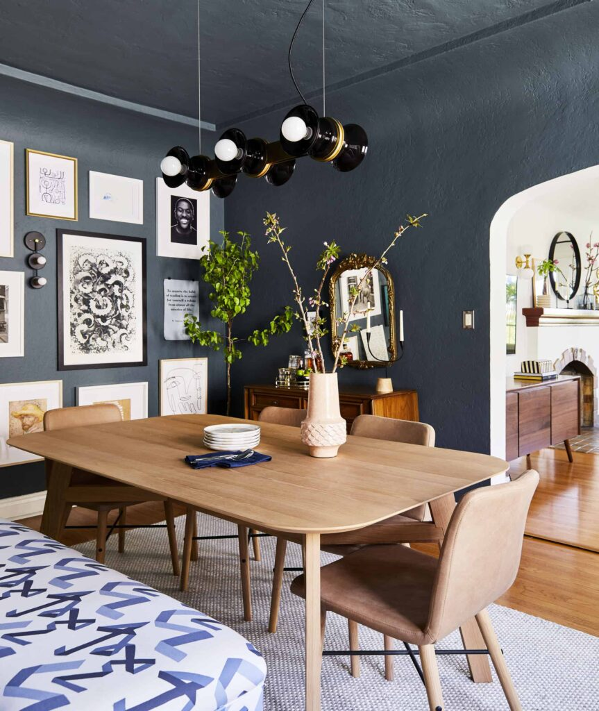 Best dark blue green paint colors: Inchyra Blue by Farrow & Ball in a dining room with curved walls and gallery wall.