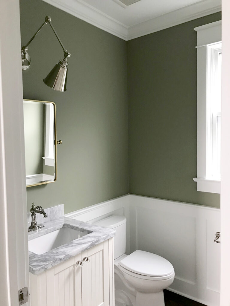 Powder room upper walls painted in Lichen by Farrow & Ball, paired with bright white wainscoting.