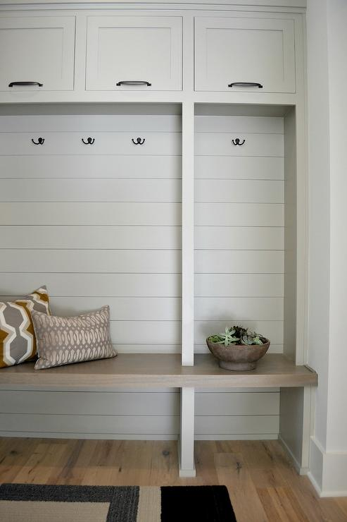 Mindful Gray built-in bench and cabinets in a minimally decorated mudroom.