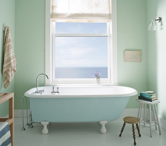 Sunny bathroom with walls painted in Palladian Blue by Benjamin Moore, with a pale blue clawfoot bathtub.