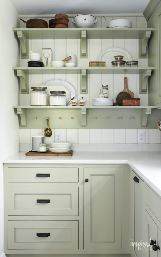 Kitchen cabinets and open shelving in Sage by Sherwin Williams.