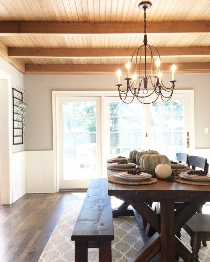 Dining room with warm wood ceiling, off-white trim and wainscoting and walls painted in Mindful Gray.