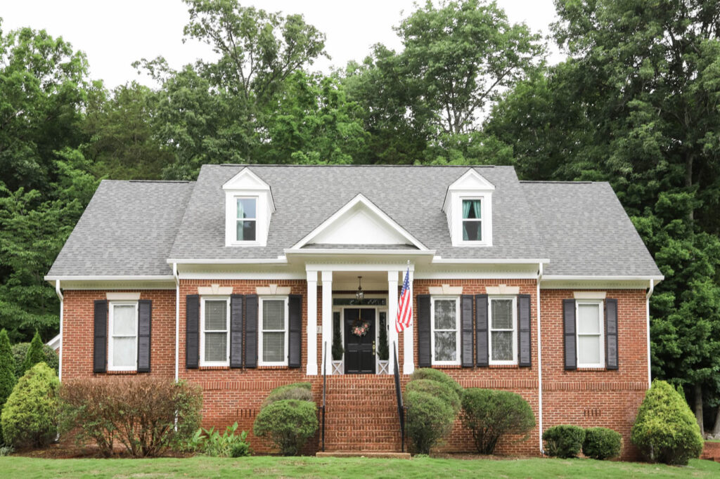 Red Brick House with White Trim and Black Shutters