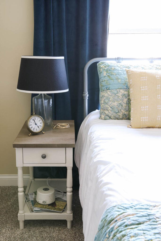 clock, noise machine and lamp in guest bedroom